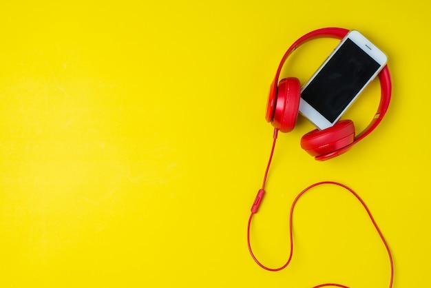 Rode hoofdtelefoon en smartphonemuziekconceptenachtergrond op geel