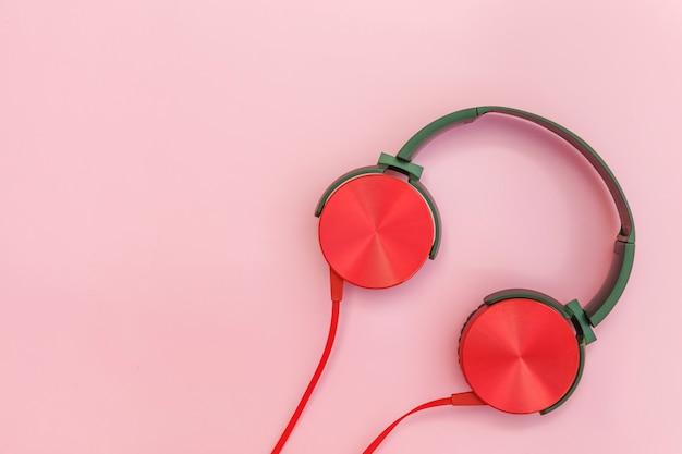 Rode hoofdtelefoon met kabel geïsoleerd op roze pastel kleurrijke achtergrond