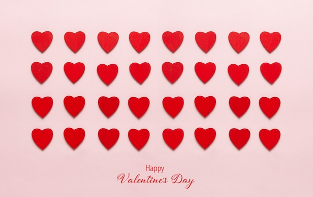Rode houten harten op de pastel roze achtergrond