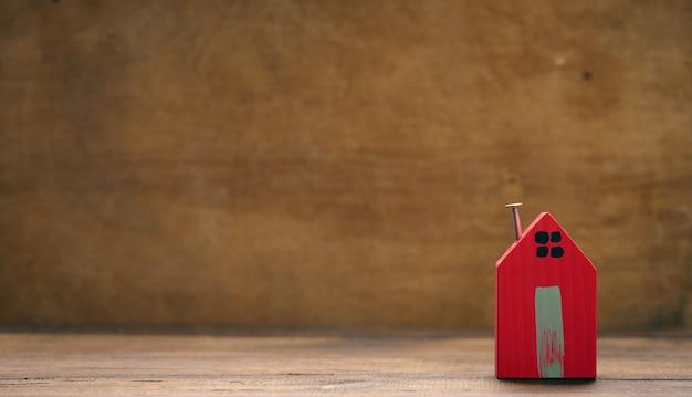 Rode houten huis op een bruine achtergrond. vastgoed verhuur, aankoop en verkoop concept. makelaarsdiensten, reparatie en onderhoud van gebouwen, kopieerruimte