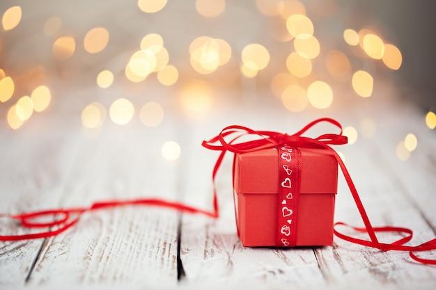 Rode huidige doos met rood striklint en papieren hart op houten tafel,