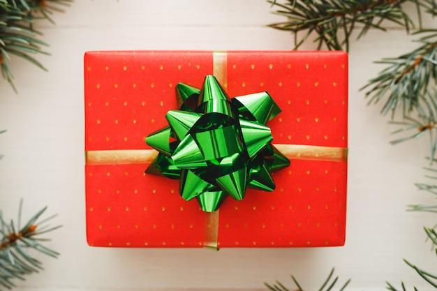 Rode huidige geschenkdoos in fir takken. kerst vakantie feest plat leggen.