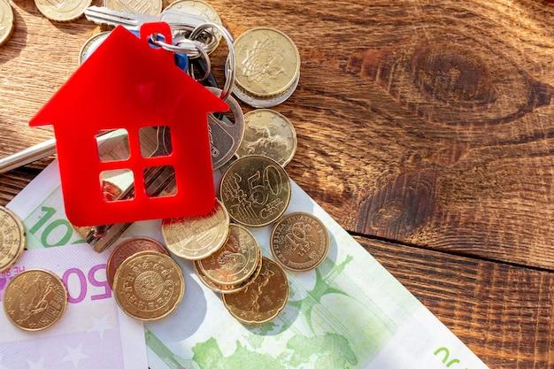 Rode huis met sleutels op de bankbiljetten en munten
