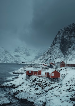 Rode hutten op een besneeuwd sakrisoy-eiland, noorwegen