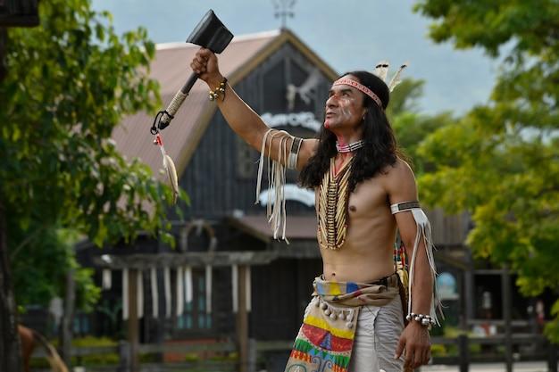 Rode indianen, indiaanse stammen, gekleed in oude kostuums, gewapend en uitkijkend naar de lucht.