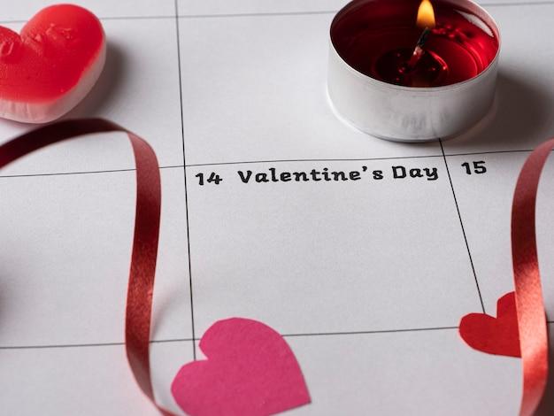 Rode kaars harten en lint op witte kalender met valentijnsdag