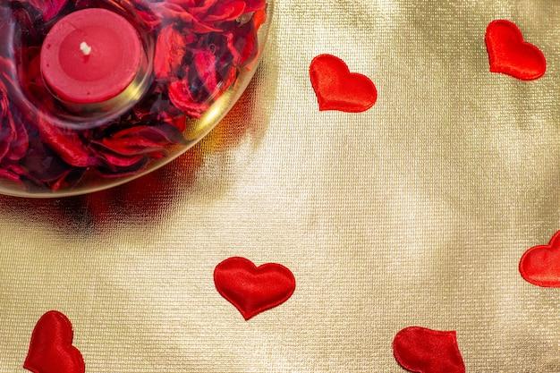 Rode kaars in een kandelaar op een gouden achtergrond met rode hartjes