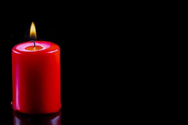 Rode kaars op zwarte achtergrond kaarslicht in het donker hoop concept gloeiende kaars close-up f