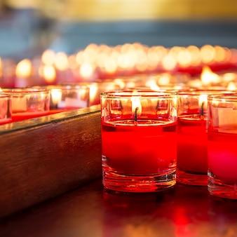 Rode kaars steekt een vuur in glas aan