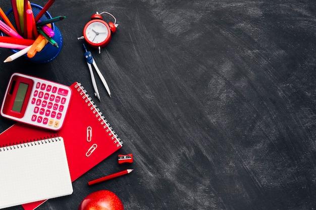 Rode kantoorbehoeften dichtbij klok en appel op bord