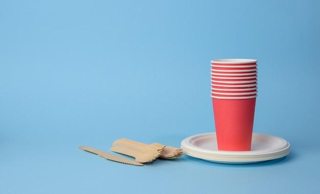 Rode kartonnen beker, witte borden en houten vorken en messen op een blauwe ondergrond. plastic afkeuringsconcept, nul afval, exemplaarruimte