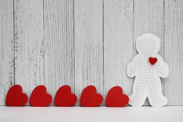 Rode kartonnen harten zijn op een rij gerangschikt. plastic figuur van een man met een rood hart.