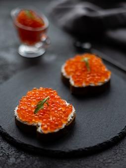Rode kaviaar in een kom en kaviaar sandwiches op een zwarte stenen bord. op een zwarte structurele achtergrond