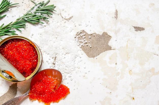 Rode kaviaar in een pot met een lepel op rustieke achtergrond