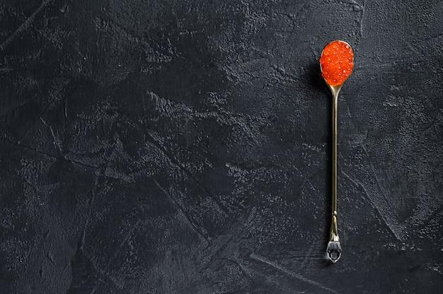 Rode kaviaar in een voortreffelijke lepel. zwarte achtergrond