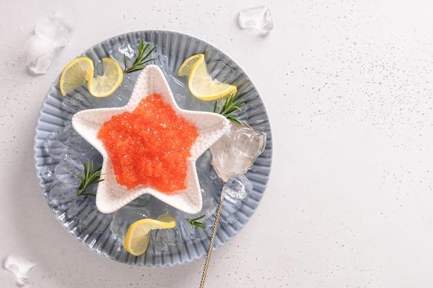 Rode kaviaar in kom in vorm van ster, geserveerd met ijsblokjes en ijsblokjes voor feest.