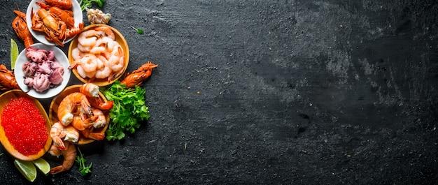 Rode kaviaar met zeevruchten, peterselie en limoenplakken op zwarte rustieke lijst