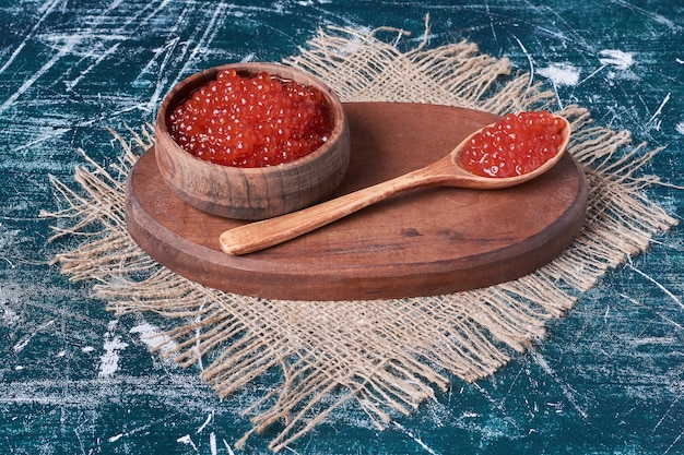 Rode kaviaar op een houten bord.