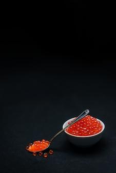 Rode kaviaar op een zwarte achtergrond. zee eten. het concept van gezonde en natuurlijke voeding. russische delicatesse.