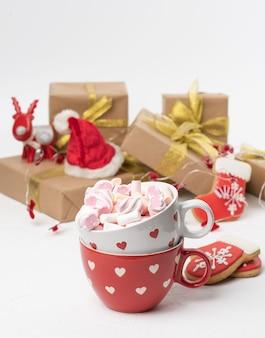 Rode keramische beker met cacao en marshmallows, achter een geschenkdoos en een kerstslinger