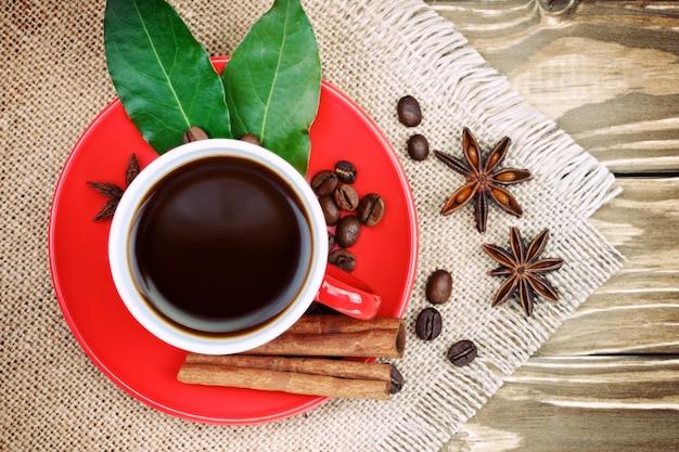 Rode keramische beker met koffietribune op houten planken en jute met verspreide koffiebonen
