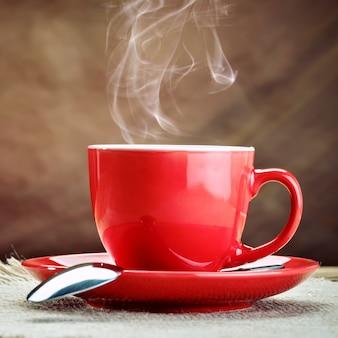 Rode keramische cup met warme koffie op houten planken.