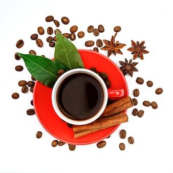 Rode keramische koffiekopje met koffie en kaneel op een witte ondergrond