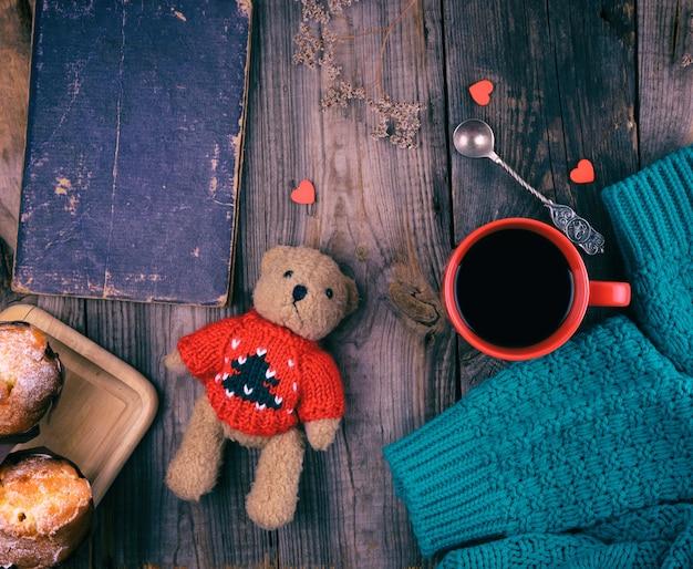 Rode keramische mok met zwarte koffie en gebakken muffins