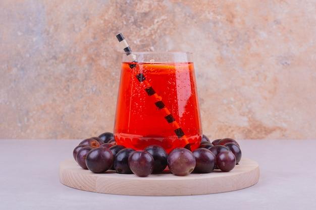 Rode kersenbessen met een glas sap op grijs.