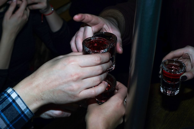 Rode kersendrank in borrelglaasjes met handen - feest in bar