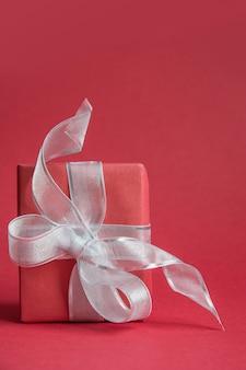 Rode kerst cadeauverpakking met zilveren lint op rood.
