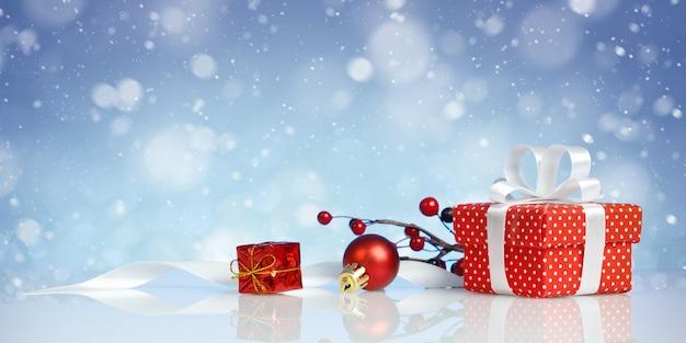 Rode kerst geschenkdoos met decoraties op blauwe muur
