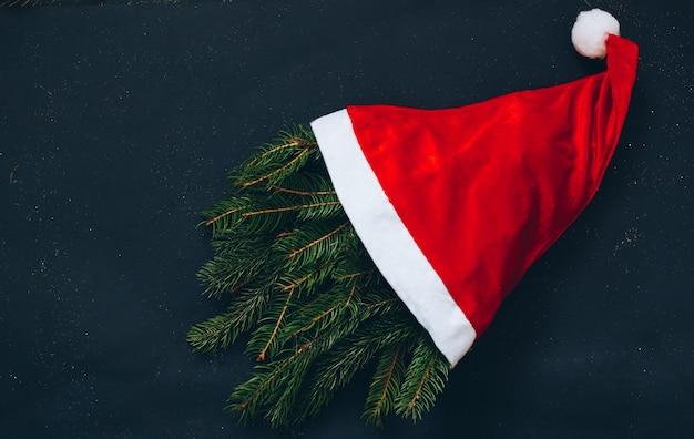 Rode kerst muts met fir tree op zwarte achtergrond. bovenaanzicht