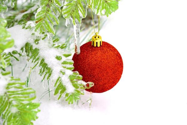 Rode kerst speelgoed bal opknoping op frosted fir tak in de sneeuw
