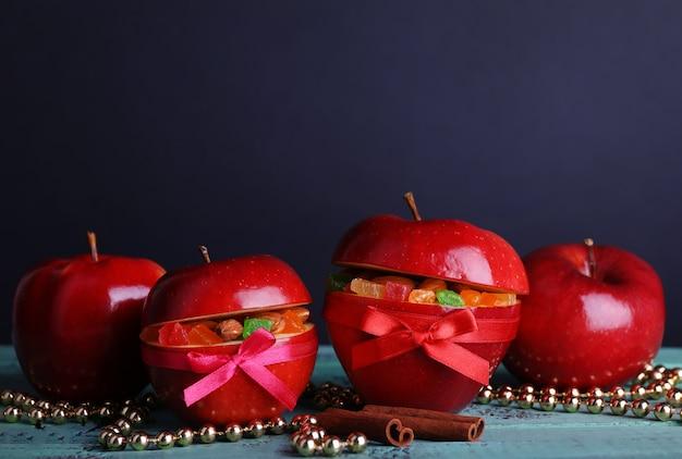 Rode kerstappels gevuld met gedroogde vruchten op een houten kleurtafel