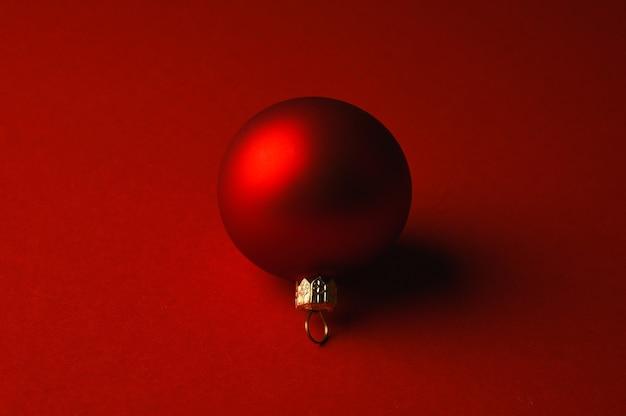 Rode kerstbal ligt op een rood oppervlak met schaduwen. hoge kwaliteit foto