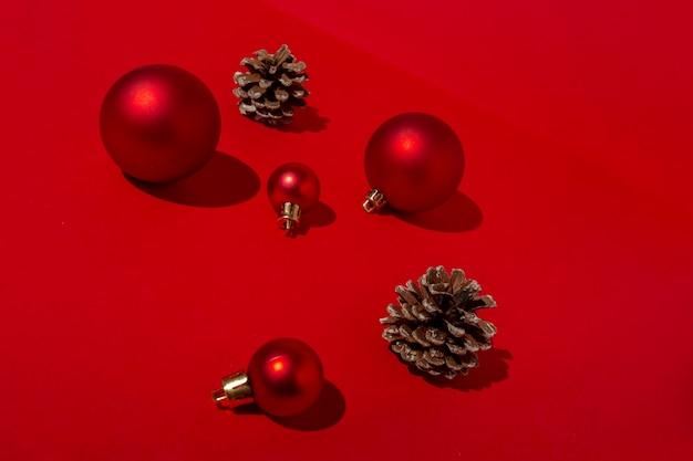 Rode kerstballen en dennenappels op rode tafel