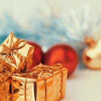 Rode kerstballen en geschenken in gouden dozen.