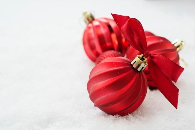 Rode kerstballen geïsoleerd op sneeuw. winter wenskaart.