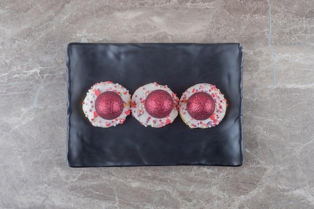 Rode kerstballen gestapeld op kleine donuts op een zwarte schaal op marmeren oppervlak