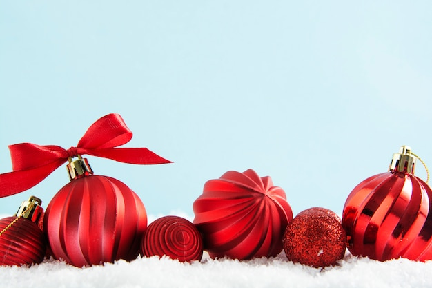 Rode kerstballen, kerstballen op sneeuw, met rood lint geïsoleerd.