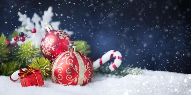 Rode kerstballen met versieringen op sneeuw