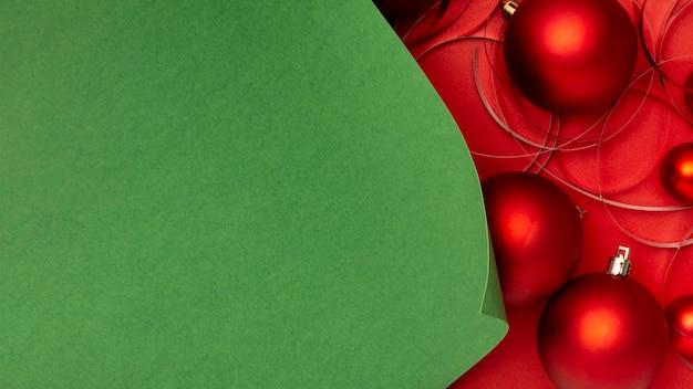 Rode kerstballen op rode tafel en groen papier