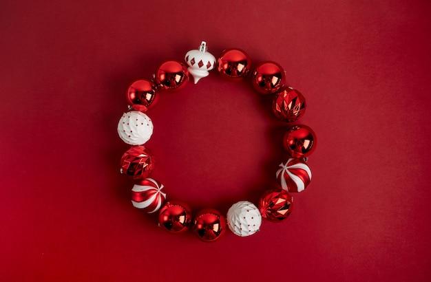 Rode kerstboom speelgoed decoratie opgemaakt als een ronde frame op een rode achtergrond met kopie ruimte. nieuwjaars wenskaart lay-out. minimale stijl. plat leggen.