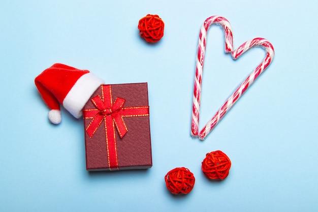 Rode kerstcadeau op een blauwe achtergrond. geschenk en snoep. kerst lay-out. vakantie. nieuwjaar. geschenken.