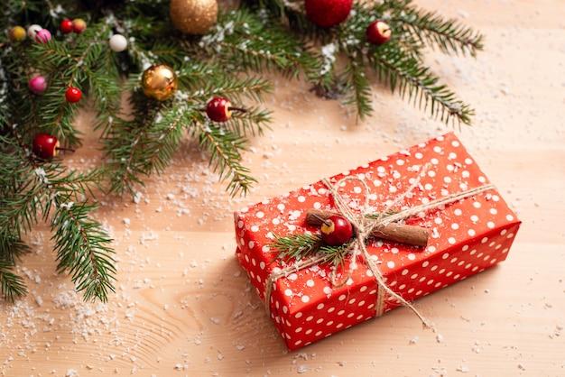 Rode kerstcadeau, versierd met touw en kaneel op de houten tafel
