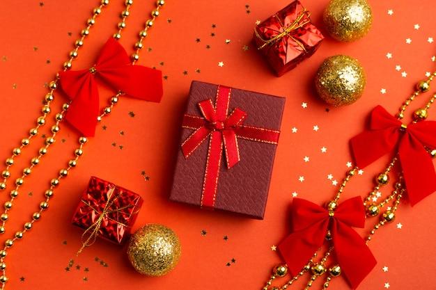 Rode kerstcadeaus en kerstbomen op een rode achtergrond. een artikel over het nieuwe jaar en kerstmis. de keuze van geschenken. een rood cadeau.