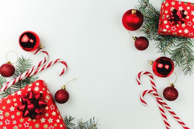 Rode kerstdecoratie op wit, kerstcadeaus, snoepjes, lolly.
