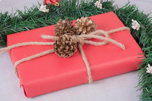 Rode kerstdoos met drie dennenappels op witte tafel.