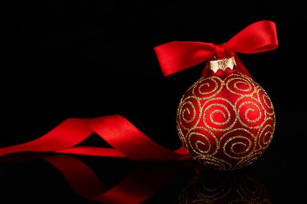 Rode kerstmisbal met boog op glanzende weerspiegelende zwarte achtergrond